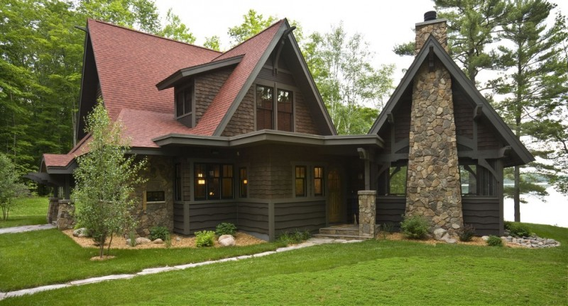 Mountain style brown two story wood exterior home with a gable roof exposed stone mortar chimney brown deck wooden wall concrete slab pathway