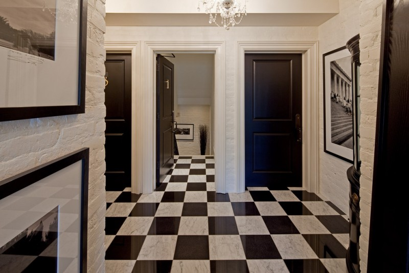 Ornate entryway with a black front door, marble floors and multicolored floors white painted brick wall black and white artworks white chandelier lamp