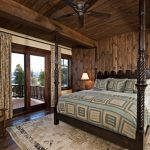 Rustic bedroom idea with beige walls and dark hardwood floors brown drapes wooden deck walls and ceiling wooden bed cream rug