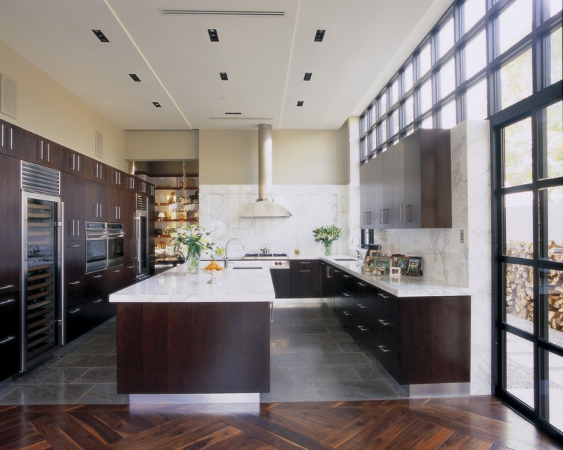 Trendy kitchen with stainless steel appliances, flat panel cabinets, dark wood cabinets, marble countertops, white backsplash, stone slab backsplash and gray floors