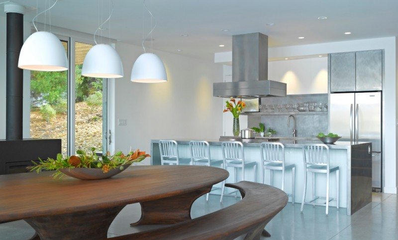 White pendant lamps wooden curved settee stainless steel countertop island and chairs white walls ceramic floors stainless steel appliances
