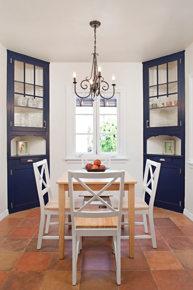 a couple of corner cabinets dining room in navy blue light toned wood dining table white finished dining chairs eathy brown tiles floors traditional pendant lamp