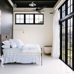 black and white bedroom 1 light maple ceiling fan industrial lamp glass sliding doors and windows with black frame white curtain white bed and floor