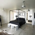 black and white bedroom black bed industrial lamps large black shelves white wall white small benches armchair