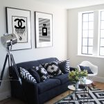 Black Sofa With Decorative Pillows Modern White Rocking Chair Layered Round Glass Top Table Area Rug With Black And White Motifs Medium Toned Wood Floors Stainless Steel Floor Lamp