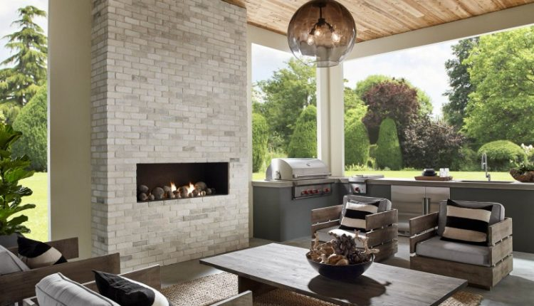 brick fireplace wooden ceiling glass pendant light wooden armchair wooden coffee table area rug stainless steel appliances