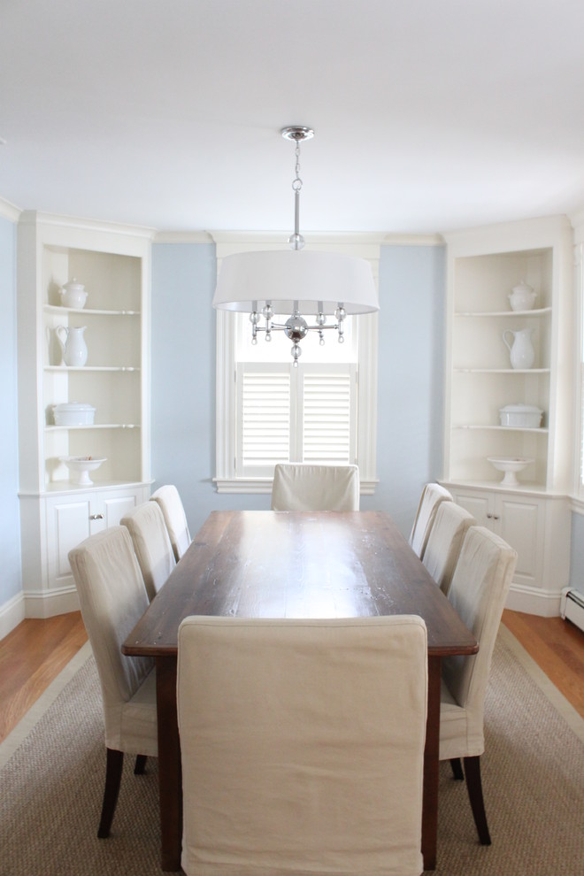 built in china cabinets in white light blue walls white ceilings hardwood dining table dining chairs with white covers medium toned wood floors white area rug
