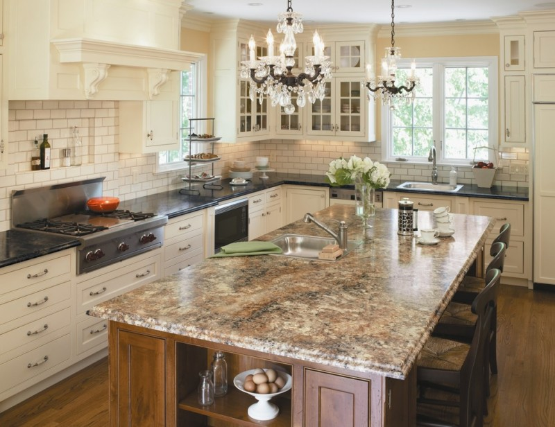 classic l shaped kitchen with beaded inset cabinets, stainless steel appliances, a drop in sink, white cabinets, laminate countertops, white backsplash and subway tile backsplash