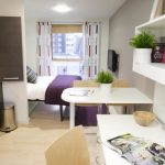 Compact Room Hideaway Kitchen Dark Flat Panel Cabinet White Open Shelves White Cabinet White Coffee Table Greenery Lightwood Floor Purple Area Rug Curtain Recessed Light