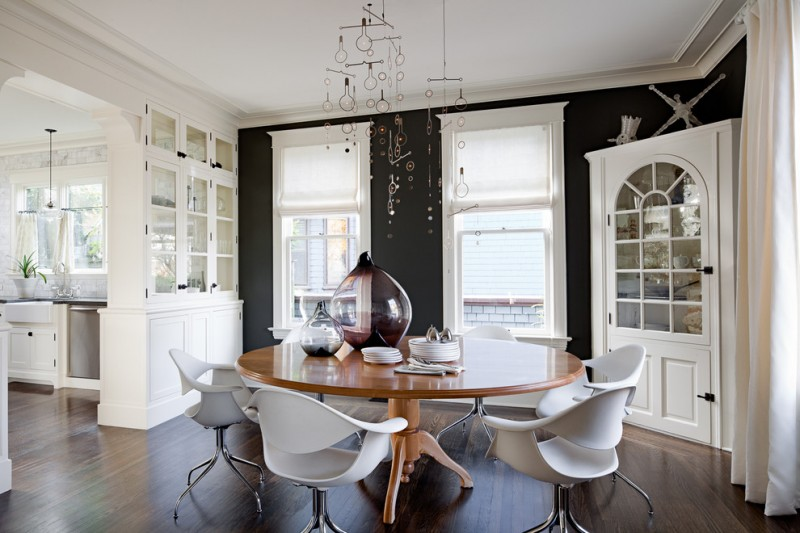 contemporary dining room white corner cabinets with arch glass door round shaped wood dining table modern white dining chairs dark toned wood floors black painted walls
