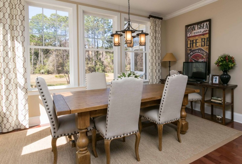 craftsman dining room long wood dining table French style dining chairs in grey grey area rug medium toned wood floors classic pendant lamp wood media console