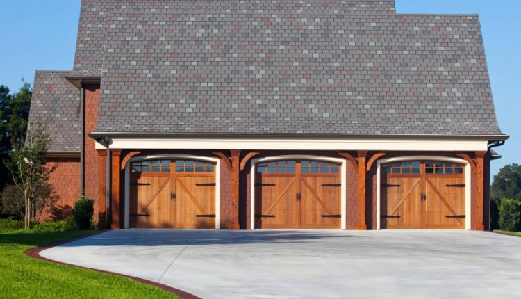 craftsman garage door three car garage red brick curved driveway wooden trim wooden door grey roof