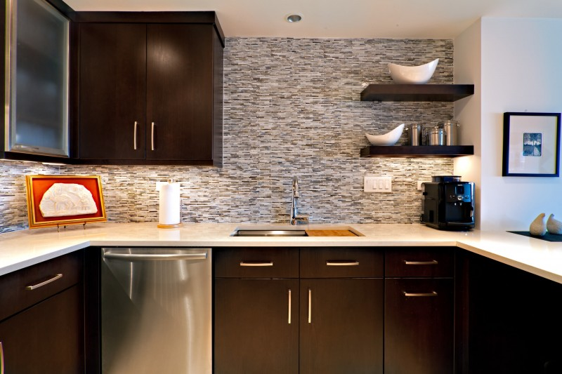 dark falt panel cabinet floating cabinet floating open shelves white countertop tiled backsplash recessed lights under cabinet lights