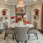 Dining Chairs With Monochromatic Motifs Built In Corner Cabinets In White Light Grey Walls Red Draperies Bronze Toned Hall Table Decorative Mirror With Bronze Toned Frame