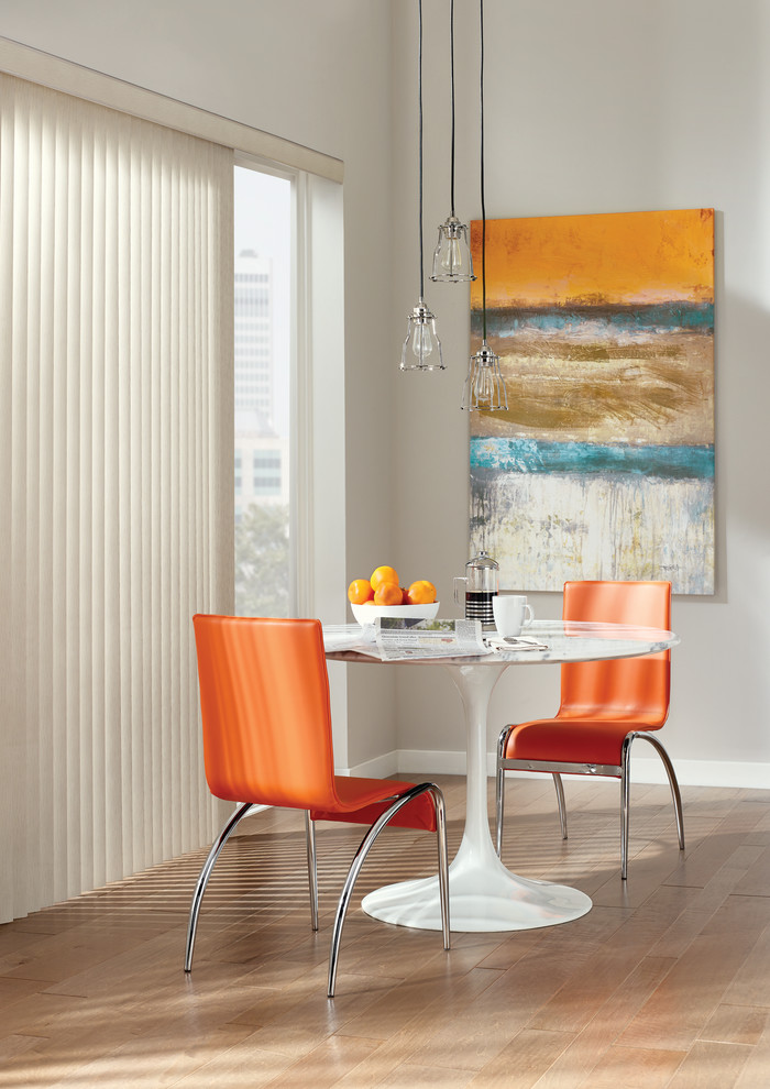 dining set with small round white table and orange sleek chairs