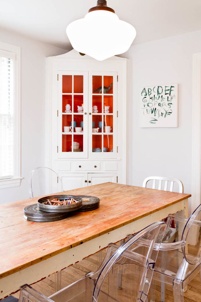 eclectic dining room idea white corner cabinet dining room with tomato red background panel wood top dining table clear acrylic dining chairs white walls medium toned wood floors