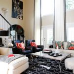 Enclosed Living Room White Sofa With Multicolored Accent Pillows Two Black Leather Chairs With Multicolored Accent Pillows White Coffee Table Patterned Area Rug White Reclaining Sofa