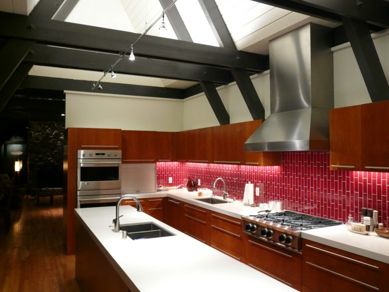 exposed beams wooden ceiling sloped ceiling track lamps red tiled backsplash metal hood flat panel cabinet white countertop wooden floor