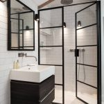 floor to ceiling shower door black trim framed mirror tiled wall marble floor white sink dark vanity rain shower
