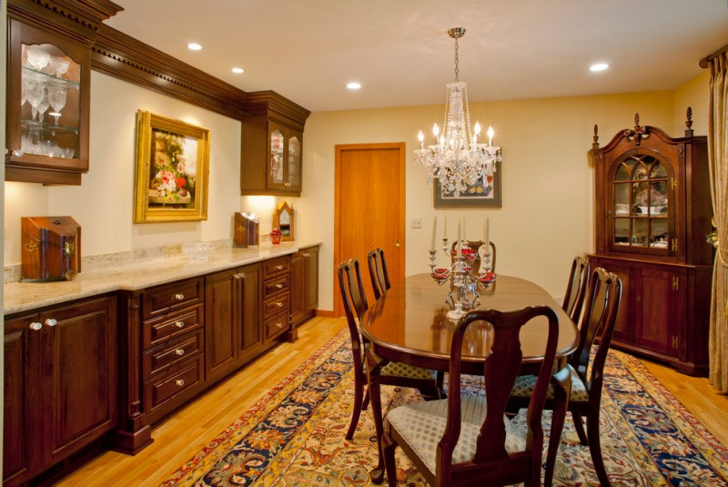 formal dining room dark hardwood corner cabinet dark hardwood dining furniture crystal chandelier white marble countertop hardwood cabinets medium toned wood floors traditional motif area rug
