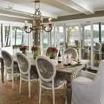 Formal Dining Room Idea French Style Dining Furniture Set A Couple Of White Chair Slipcovers Brown Area Rug Dark Hardwood Floors Gold Toned Chandelier