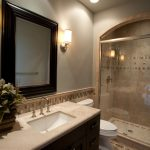 Framed Mirror Granite Countertop Under Mount Sink Dark Vanity Mosaic Tile Arched Shower Area Wall Sconce