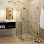 frameless glass shower doors bathrobes patterned wall cream tiles antique chandelier floating vanity and mirrors