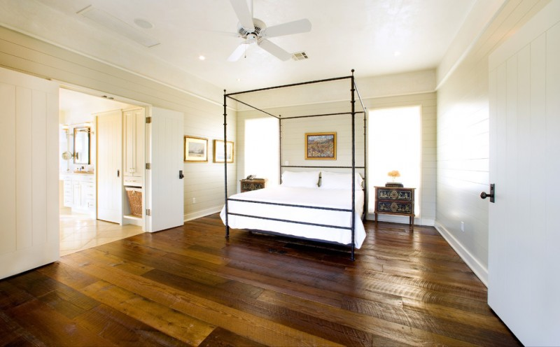large rustic master bedroom with beige walls, dark hardwood floors and brown floors white fan white painted doors white deck wooden walls