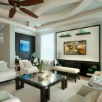 large transitional living room with green walls and a wall mounted TV wooden hanging fan black painted door less cabinet white sofa and pillow throws glass coffee table