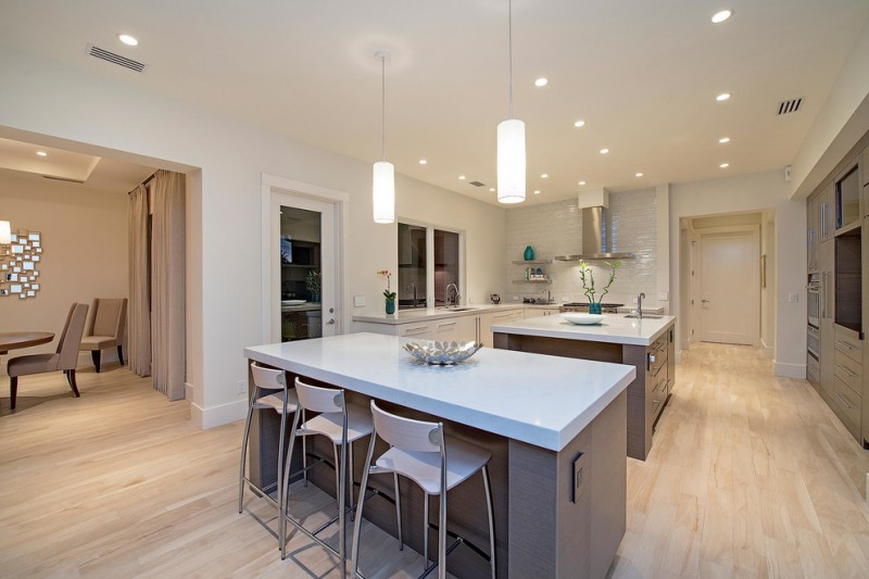 large transitional u shaped eat in kitchen with an undermount sink, flat panel cabinets, gray cabinets, quartz countertops, white backsplash, porcelain floors, multiple islands and stainless steel appl