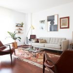 Living Room With Brown Leathered Chairs, Beige Sofa, Warm Orange Rug, Glass Top Coffee Table, Geometric Lines Floor Lamp, Wall Shelves