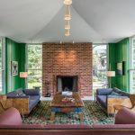 Living Room With Green And White Wall, Bricks On Fireplace, Blue Grey And Purple On Sofas, Brown Marble Coffee Table, Green Rug, Floor Lamp