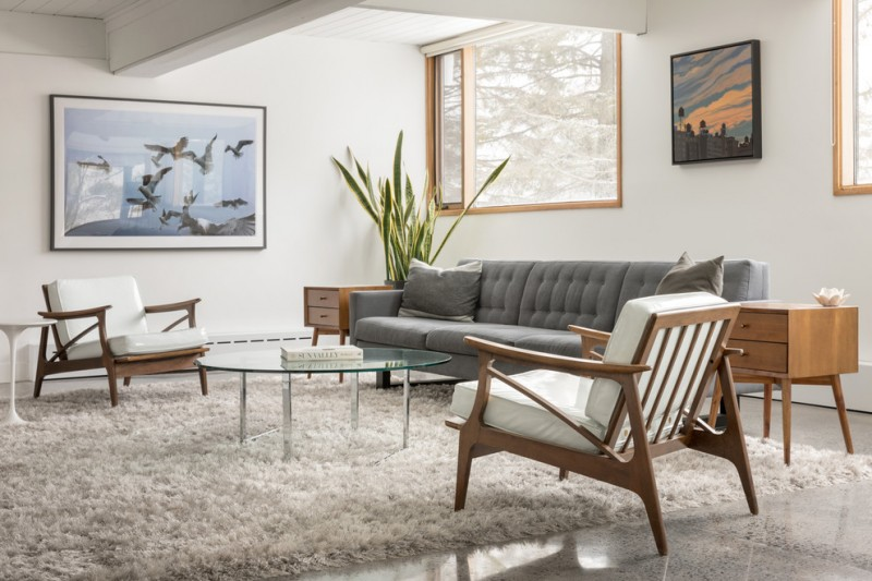 living room with wooden chairs with shite cushion, steel round coffee table with glass top, grey long sofa, wooden shelves