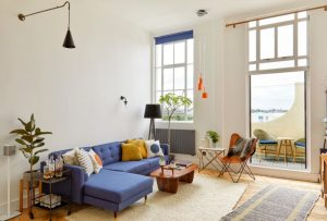 living roomwith beige rug, orange plastic midcentury chair, blue sofa, wooden coffee table, black floor lamp