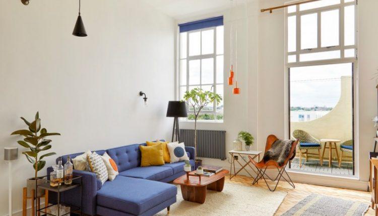 living roomwith beige rug, orange plastic midcentury chair, blue sofa, wooden coffee table, black floor lamp