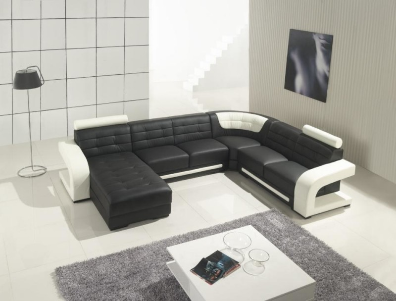 modern black sectional with white accent and additional facing chaise high end white coffee table grey shag carpet white floors modern floor lamp