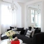 Modern Black Sofa With Black And Grey Accent Pillows Round Glass Top Center Table With Red Books And Vivid Decorative Flowers White Area Rug White Walls Crystal Chandelier