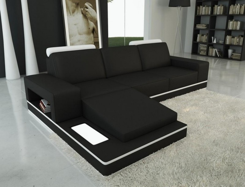 modern solid black sectional with white accent headrests and additional chaise with under shelf fluffy white area rug white floors