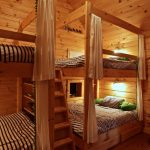 queen size bunk beds lodge bedroom natural wood bunk beds black and white stripe bed sheets and pillow cover whitebed curtain with green tassels built in wood ladder