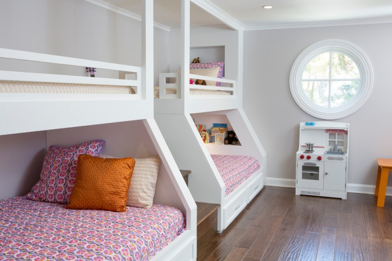queen size bunk beds purple patterned bed sheets and pillow covers white bunk beds wood flooring large circle window recessed lighting