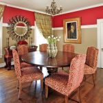 Red Patterned French Style Dining Chairs Circular Wood Dining Table With Darker Finishing Dark Toned Wood Floors Decorative Mirror Over Buffet Red & Beige Walls
