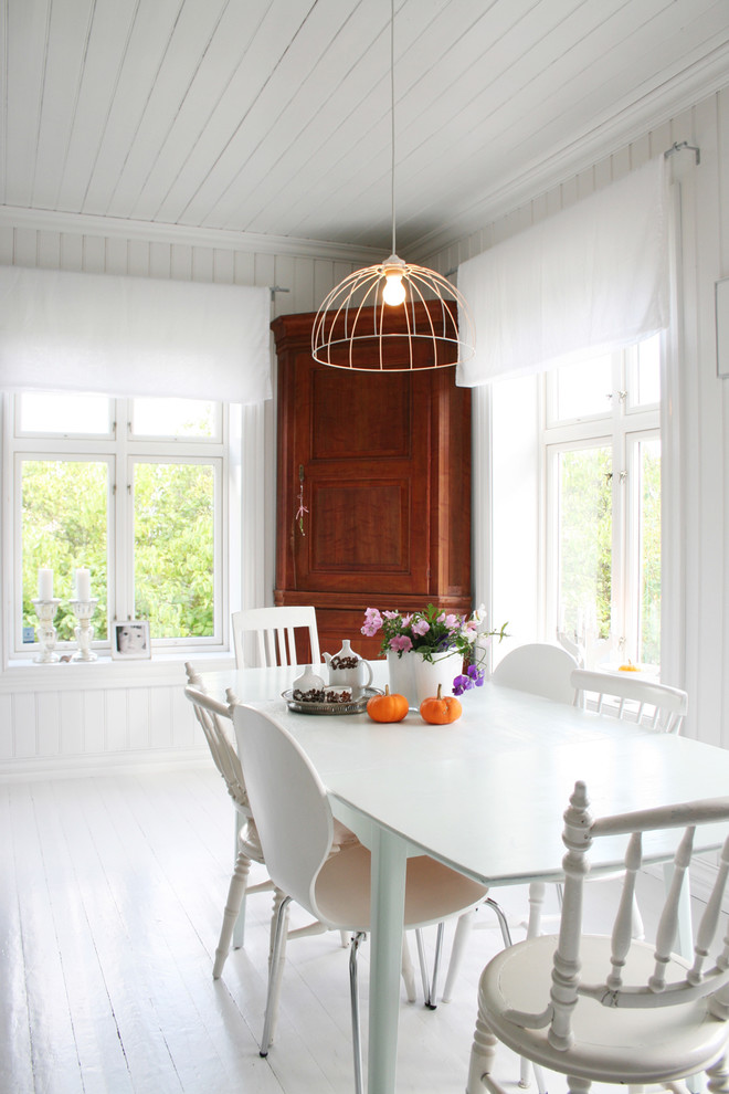 scandinavian dining room in white wood corner cabinet white dining chairs white dining table white ceramic tiles floors white walls white ceilings unique pendant lamp with warm lights