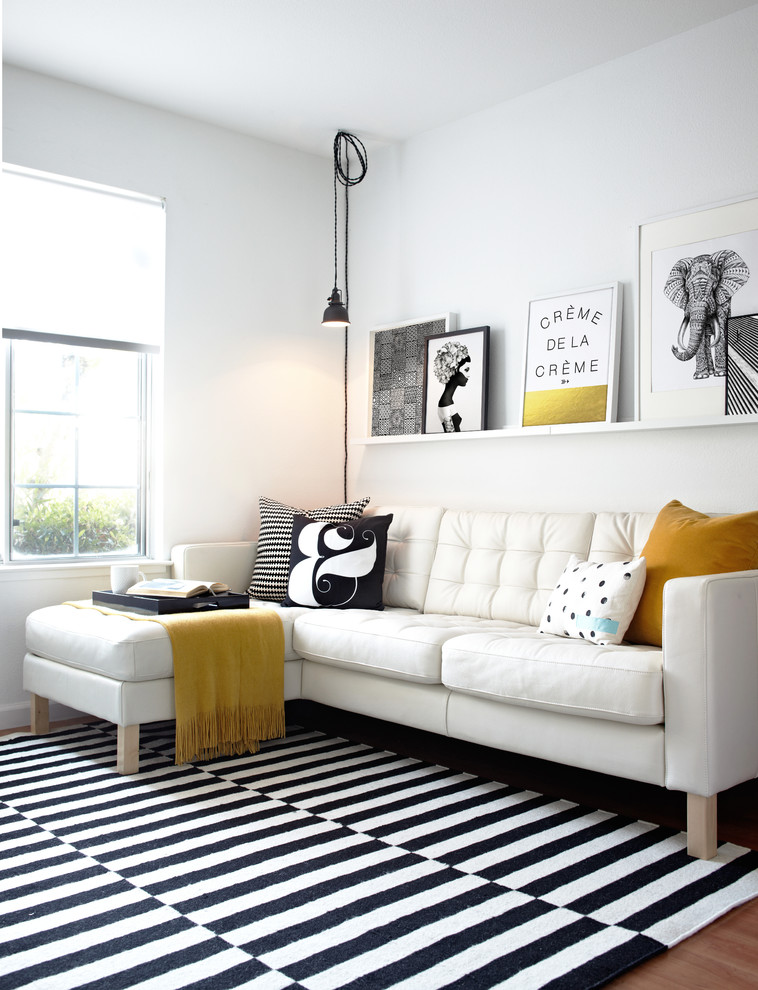 scandinavian living room white sofa with black & white throw pillows white & black stripes area rug single shelf in white wall ornaments