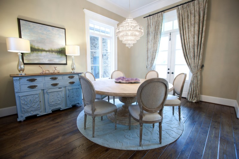 shabby chic dining nook with soft toned French dining chairs round top wood dining table round area rug in white dark hardwood floors wood top hall console crystal chandelier