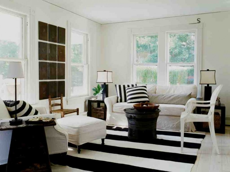 shabby chic living room white chair slipcover with white black stripped accent pillows white table slipcover white chair white black stripped area rug white walls white ceramic tiles floors