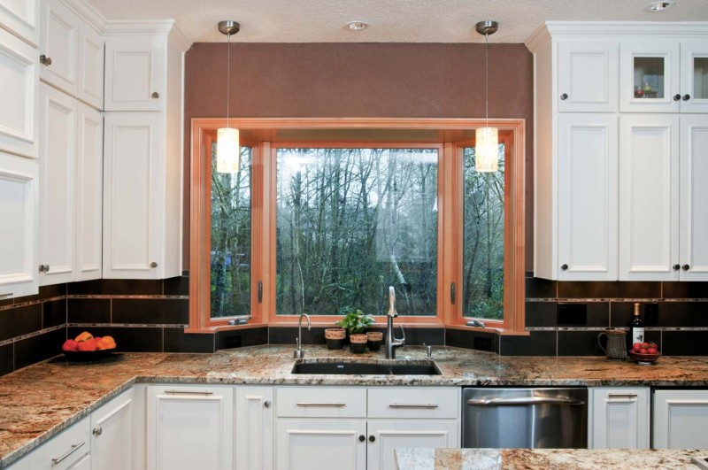 small bay window brown trim granite countertop white cabinet under mount sink ceiling lights
