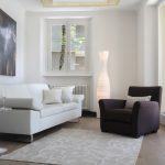 Small Contemporary Living Room White Sofa With White Throw Pillows Black Armchair With Bright Cased Pillow Medium Sized White Rug Unique White Floor Lamp Small White Side Table With Round Top