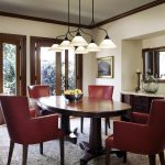 Traditional Dining Room French Dining Chairs With Red Leather Cover Dark Finishing Table Area Rug With Traditional Motifs Traditional Chandelier Light Beige Walls Wood Framed Glass Windows