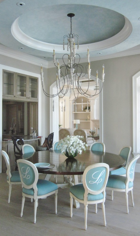 traditional dining room dark finished dining table with white base French dining chairs with aqua sunbrella covers classic chandelier