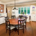 Traditional Dining Room White Recessed Corner Cabinets In Asymmetric Shape Dark Toned Wood Floors Round Top Wood Dining Table Dark Finished Wood Dining Chairs Classic Pendant Lamp